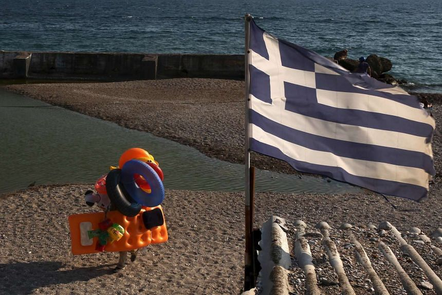 A beach vendor walks on the beach while a Greek flag flutters at a southern Athens suburb.