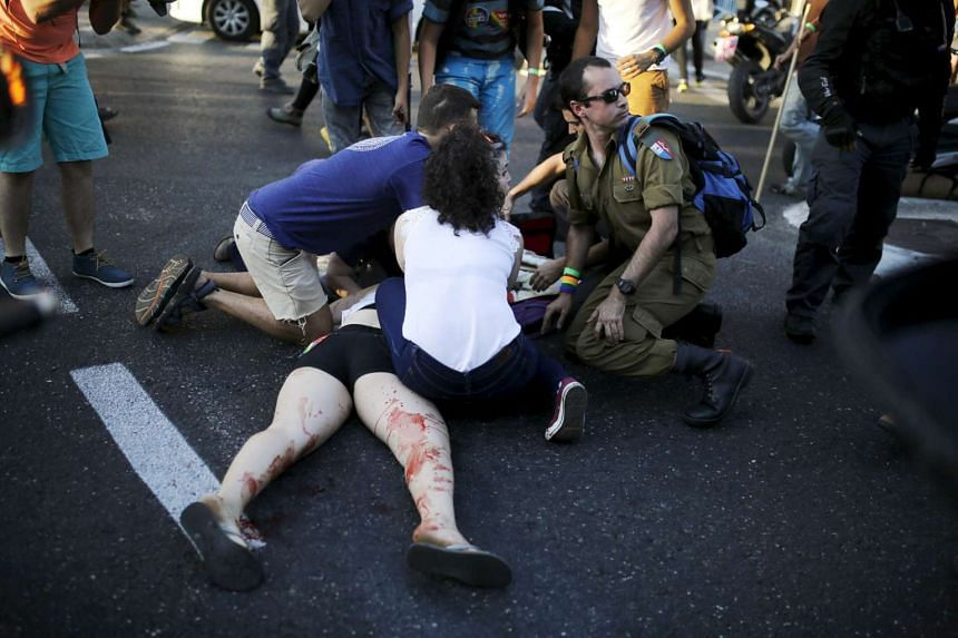 Participants of a gay pride parade in Jerusalem treat an injured person.