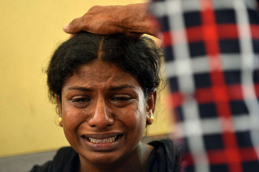 A Sri Lankan woman weeps as her wounded husband is admitted to the main hospital in Colombo.