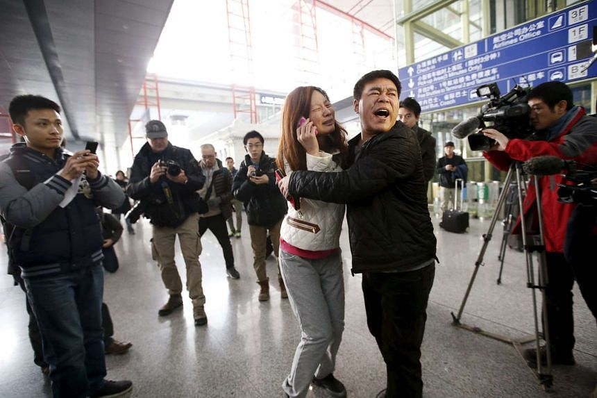 A relative (woman in white) of a passenger onboard Malaysia Airlines flight MH370 cries as she talks on her mobile phone at the International Airport in Beijing on March 8, 2014.