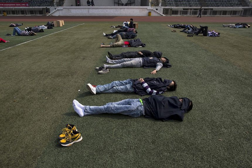 Workers take a nap during lunch break at a Foxconn factory in Shenzhen, Guangdong province in this January 21, 2015 file photo.