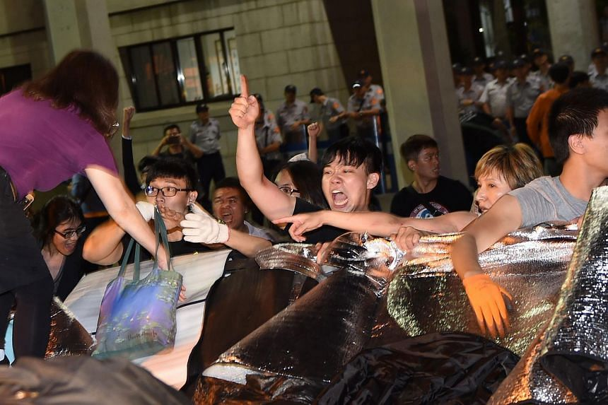 Protesters cross a barbed wire fence outside the Education Ministry during a demonstration in Taipei early on July 31, 2015.