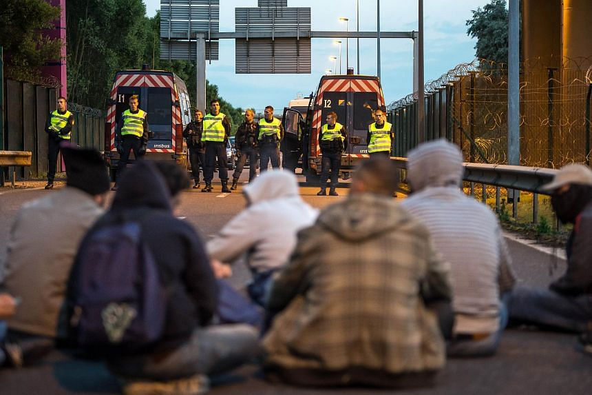 French gendarmes stand facing a group of seated migrants as they block their way in the Eurotunnel site near Calais, northern France, on July 30, 2015.