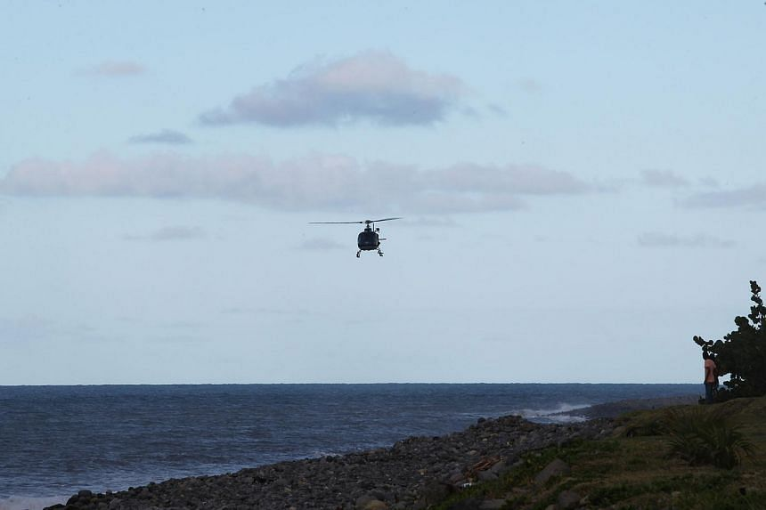 A French Police helicopter flies at low altitude as part of a search for debris in the east of the French Indian Ocean island of La Reunion, on July 30, 2015.