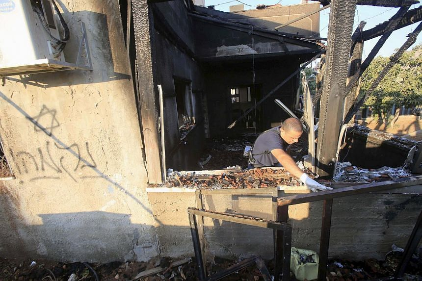 An Israeli police officer inspects a house damaged by Jewish extremists in Doma, near the West Bank city of Nablus on July 31, 2015.
