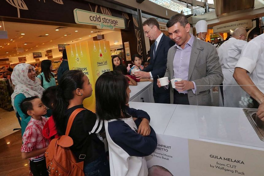 The Straits Times editor Warren Fernandez (right) and Marina Bay Sands CEO George Tanesijevich (left) serve ice-cream and gelato to 30 children from the ST School Pocket Money Fund to kick-start the Scoops of Hope charity event.