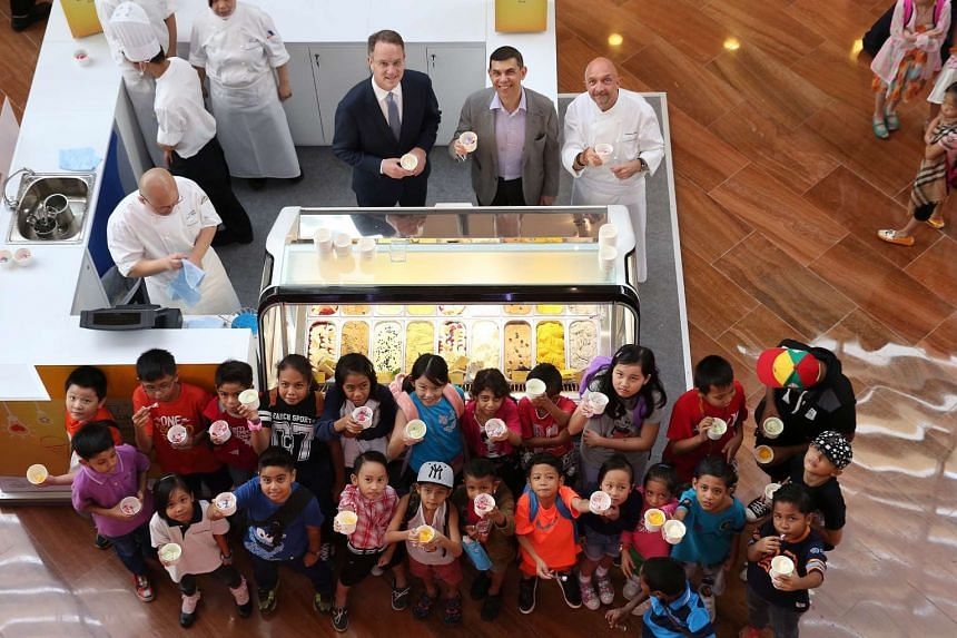 The Straits Times editor Warren Fernandez (in grey) and Marina Bay Sands CEO George Tanesijevich (in black) serve ice-cream and gelato to 30 children from the ST School Pocket Money Fund to kick-start the Scoops of Hope charity event.