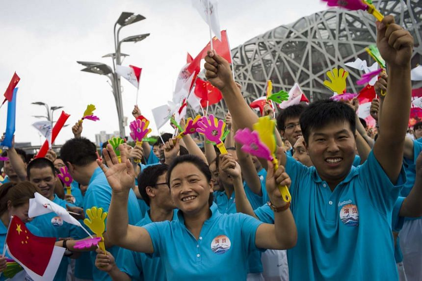 Volunteers react a few minutes before the announcement by the International Olympic Committee in Beijing on July 31, 2015.