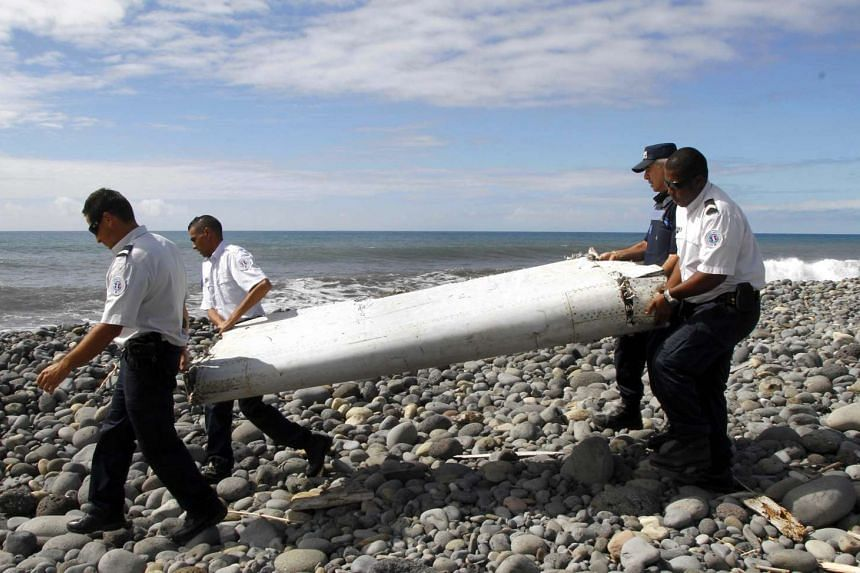 Officers carrying pieces of debris from an unidentified aircraft on the island of La Reunion on July 29, 2015.