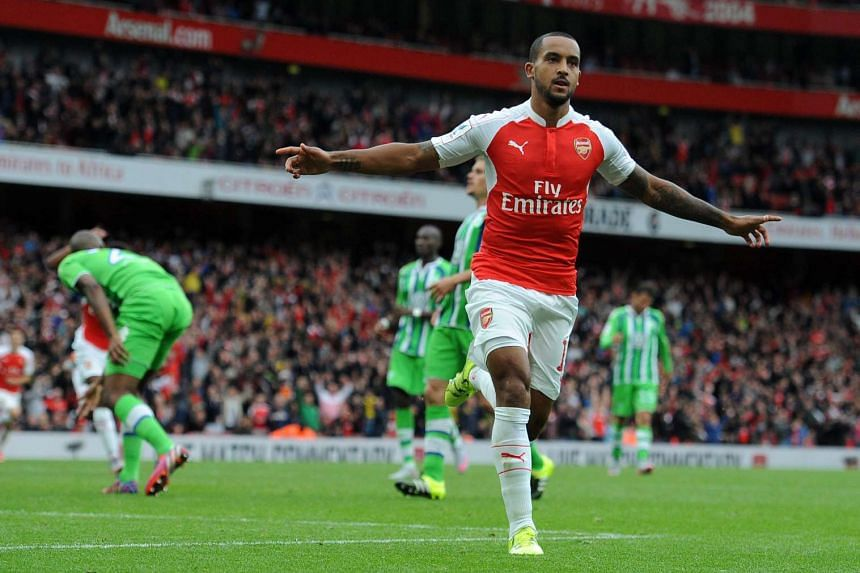 Arsenal's Theo Walcott celebrates after scoring during an Emirates Cup soccer match between Arsenal and VFL Wolfsburg at the Emirates Stadium in London, Britain, on July 26, 2015.