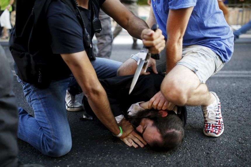People disarm an Orthodox Jewish assailant shortly after he stabbed participants at the annual Gay Pride parade.