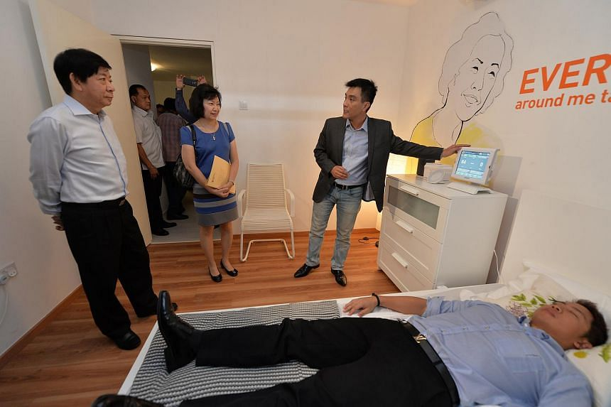 National Development Minister Khaw Boon Wan (left) and HDB CEO Cheong Koon Hean watching a demonstration of a device that can monitor an elderly resident in bed.