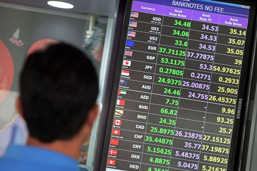 A tourist looks at an electronic board displaying exchange rates in Bangkok on July 27, 2015.