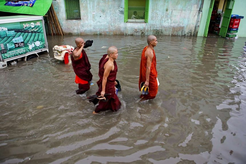 Buddhist monks walk pass along flooded road at downtown area of Yangon, Myanmar on July 31, 2015.