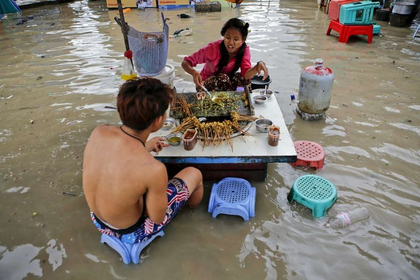 A girl sells food in water at downtown area of Yangon, Myanmar on July 31, 2015.