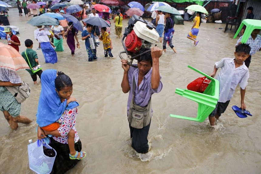 People walk pass around flooded road at downtown area of Yangon, Myanmar on July 31, 2015.