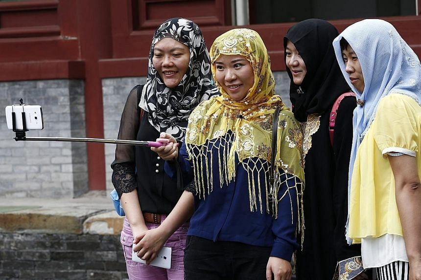 Muslims taking a photograph after morning prayers outside the Niujie Mosque in Beijing on July 18. Islam is one of China's fastest growing faiths, and the proportion of Muslims in the country is expected to hit 2.7 per cent in 2050, from 1.8 per cent