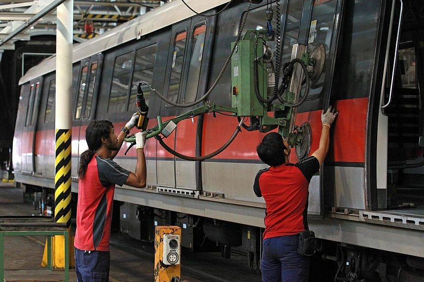 SMRT staff carrying out inspection and maintenance of trains at the Bishan depot. The rail operator has seen drooping profits as it expands its network and fleet of trains amid an ageing rail system.