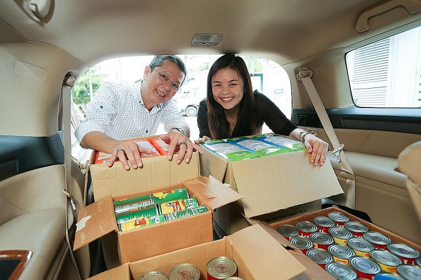 Social supermarket Saltsteps founder Desiree Yang with her father, Mr Roland Yeo. Ms Yang's social enterprise collects food and disposable goods that suppliers cannot sell, and sells them to needy families at a discount.