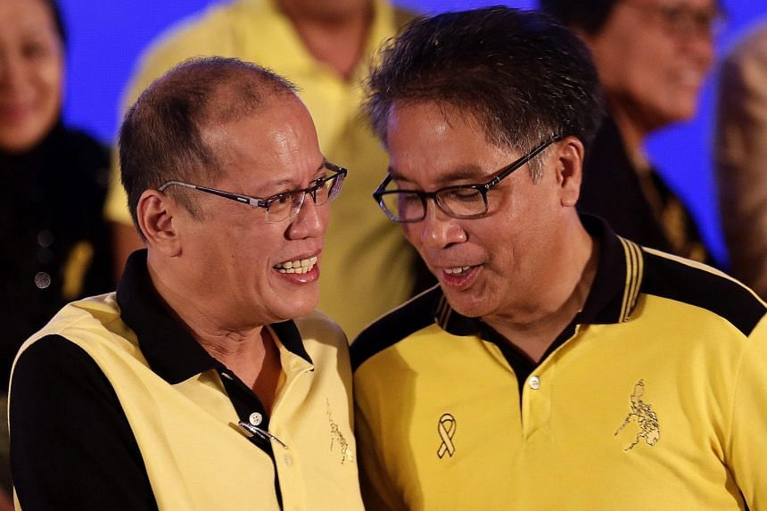 """President Benigno Aquino (left) shaking hands with Mr Mar Roxas at a political party gathering in San Juan city, eastern Manila, yesterday. Mr Aquino has singled out Mr Roxas for the latter's """"integrity, mettle and readiness for the job""""."""