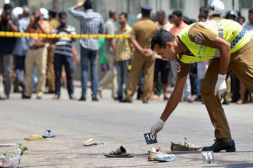 A police officer at the scene of a shooting in the Sri Lankan capital Colombo yesterday, where a woman was killed and 12 others were wounded. The unidentified gunmen sprayed bullets into the crowd just after Finance Minister Ravi Karunanayake left th