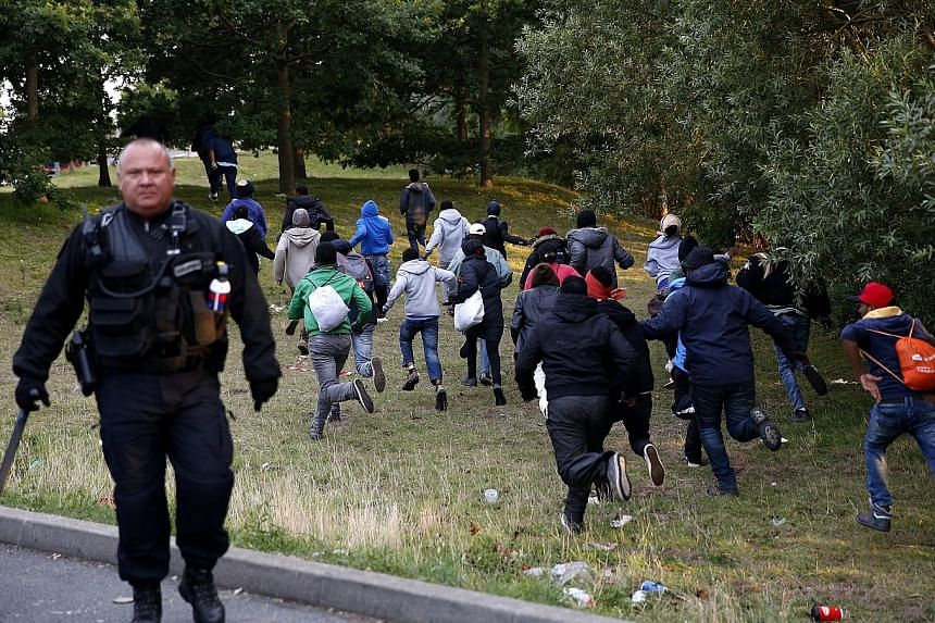 Migrants from the makeshift refugee camp in Calais, France, trying to escape from the French police on Thursday as they attempt to catch a train to reach Britain via the Channel Tunnel.