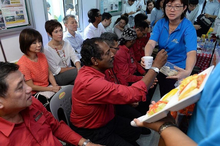 Bus captains trying out healthier food options recommended by the Health Promotion Board, at the SMRT Choa Chu Kang bus interchange, as Senior Minister of State for Health and Manpower Amy Khor (back row, in red) and Senior Minister of State for Fina