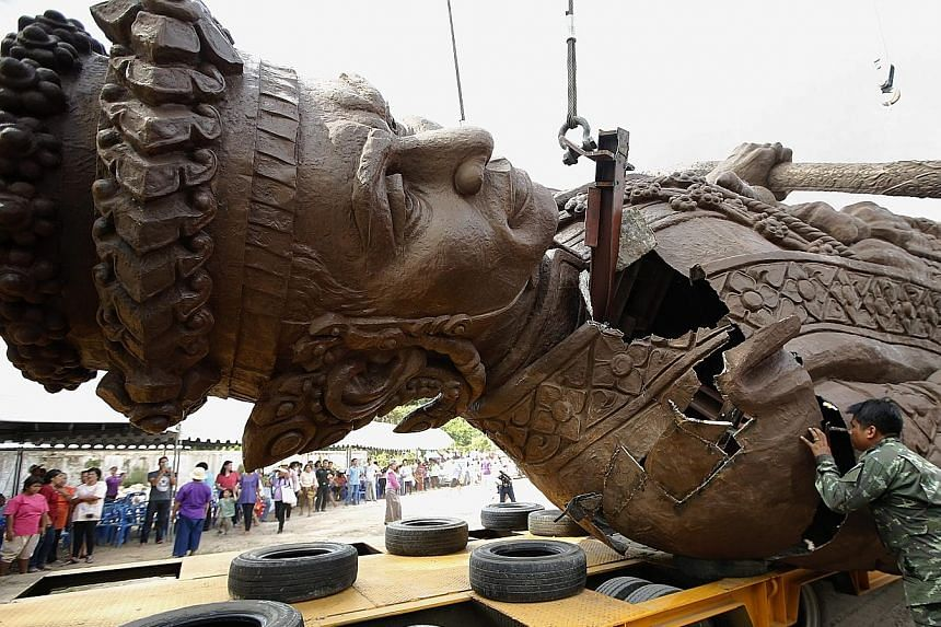 Meanwhile, a Thai soldier inspects damage to a statue of King Narai the Great, caused during its transportation to the park in Hua Hin.