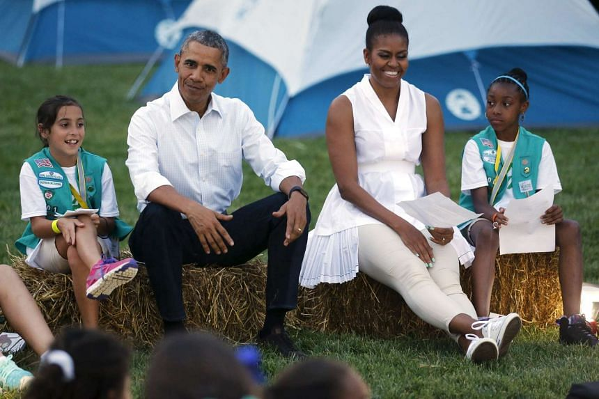 US President Barack Obama and First Lady Michelle Obama at a camp-out for Girl Scouts on the South Lawn of the White House on June 30, 2015. Obama has been encouraging US students to pursue degrees in the Science, Technology, Engineering and Mathema
