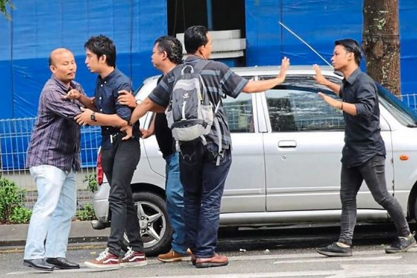 Officers arresting the men at the entrance of the Dang Wangi police headquarters.