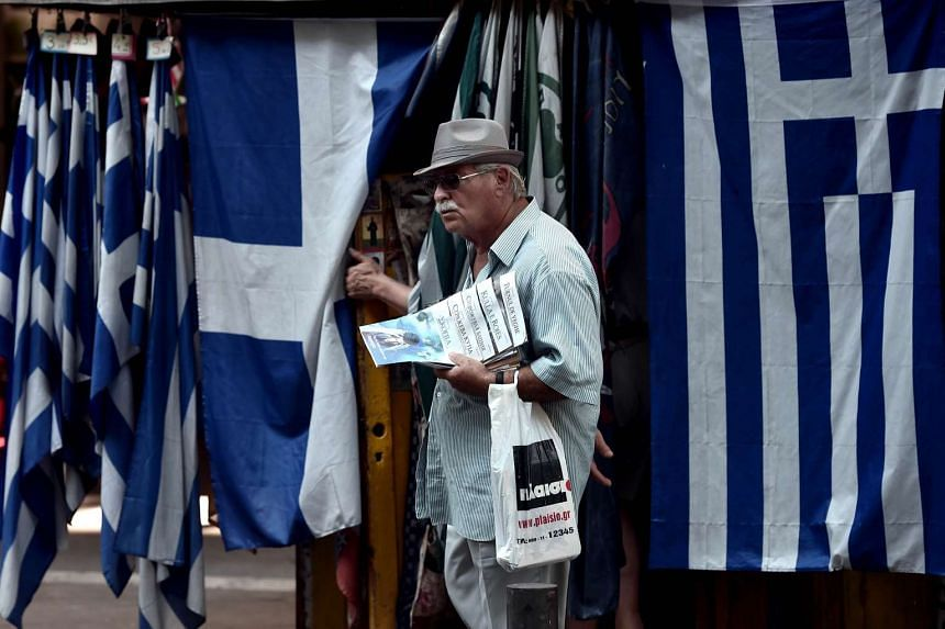A man stands in front of Greek flags in central Athens on July 31, 2015.