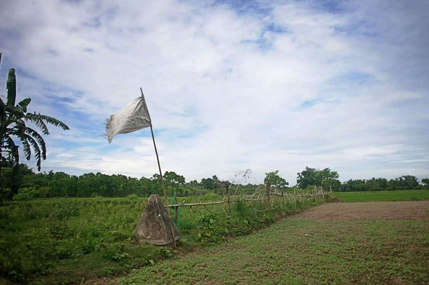 A flag on a piller indicating the border line of India and Bangladesh at Dahagram-Angarpota enclave on July 31, 2015.