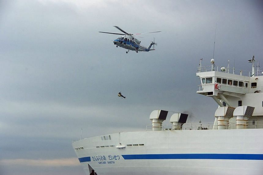 A handout picture taken and provided on 01 August 2015 by the Japan Coast Guard shows a Coast Guard helicopter flying over the Sunflower Daisetsu car ferry off Tomakomai port, Hokkaido, Japan.