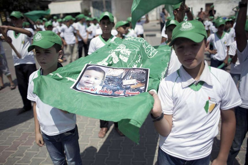 Palestinian children carry a funeral stretcher with a picture of 18-month-old Ali Saad Dawabsha, during a demonstration simulating a funeral ceremony.