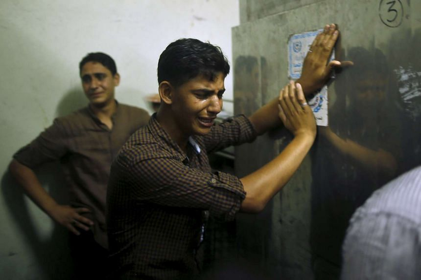 Friends of Palestinian Mohammed Al-Masri mourn at a hospital morgue in the northern Gaza Strip.