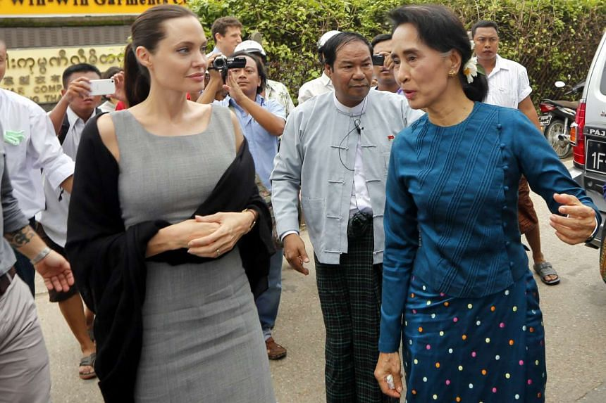 Angelina Jolie (left) and Aung San Suu Kyi (right) arriving at a slum area on August 1, 2015.