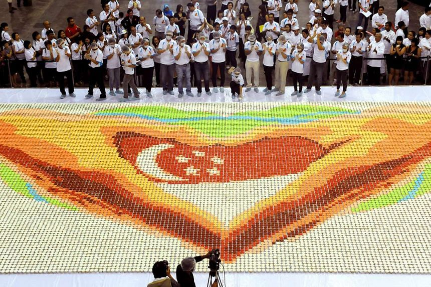 Young people from Singapore baked their way to a Guinness World Record by making the world's largest cupcake mosaic at the Singapore Expo on July 29, 2012.