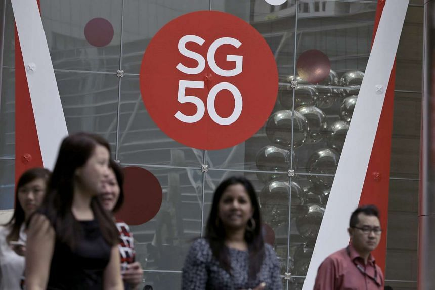 People walking in front of an SG50 logo.