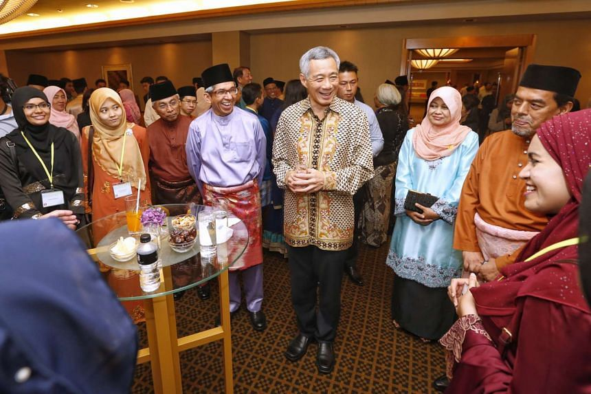 Prime Minister Lee Hsien Loong (fifth from left) and Communications and Information Minister Yaacob Ibrahim (fourth from left) attending a Hari Raya dinner for community leaders yesterday. Dr Yaacob announced at the event that Istana Kampong Gelam