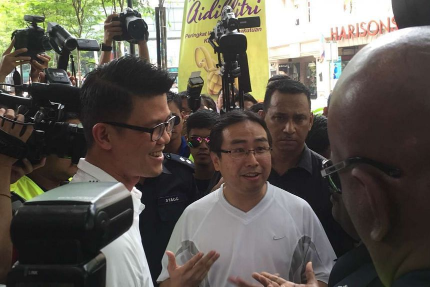Tan Kar Hing (left) and Chang Lih Kang (right) talking to police at a rally calling for the Prime Minister's resignation at Sogo Shopping Complex on Saturday, August 1, 2015.