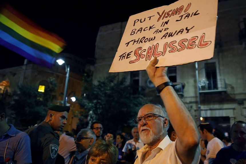 A man holds a placard as thousands of Israelis from the gay community and supporters gather in downtown Jerusalem on Aug 1 to protest against gay discrimination.