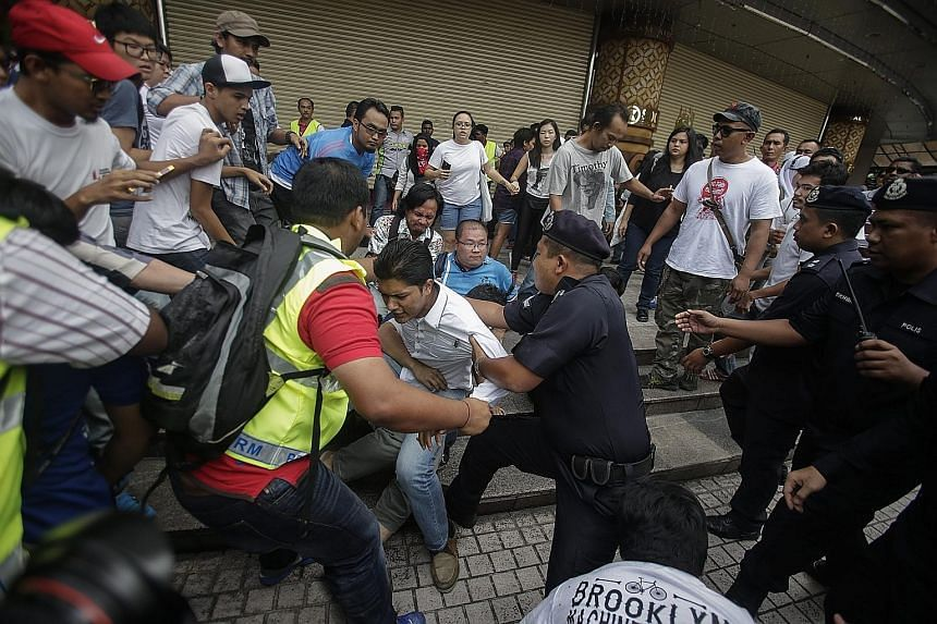 Supporters of the #TangkapNajib (Arrest Najib) protest clashing with the Royal Malaysia Police in Kuala Lumpur yesterday. About 100 people took part in the demonstration.