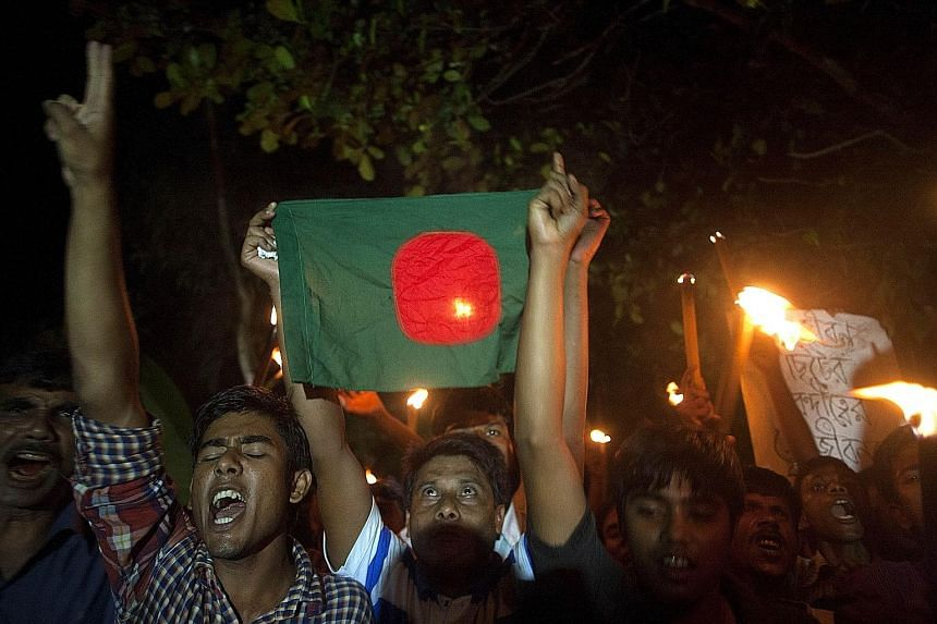 """Residents of the Dashiar Chhara enclave, which belonged to India but has become part of Bangladesh, take to the streets in celebration yesterday. The Bangladesh government will roll out a """"fast-track masterplan"""" to develop the enclaves, building new"""
