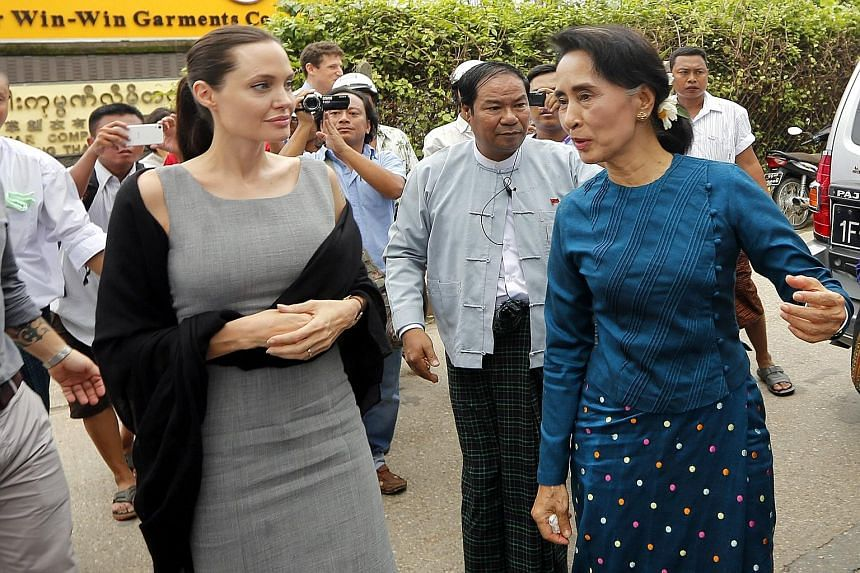 American actress Angelina Jolie (left) and Myanmar's opposition leader Aung San Suu Kyi (in blue) arriving at a slum area in the Hlaing Thar Yar township in Yangon yesterday. The Oscar-winning star, who is on a six-day visit to Myanmar as the goodwil