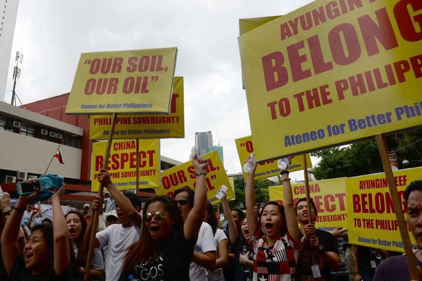 Anti-China protesters shout slogans during a protest in front of the Chinese consulate in Manila.