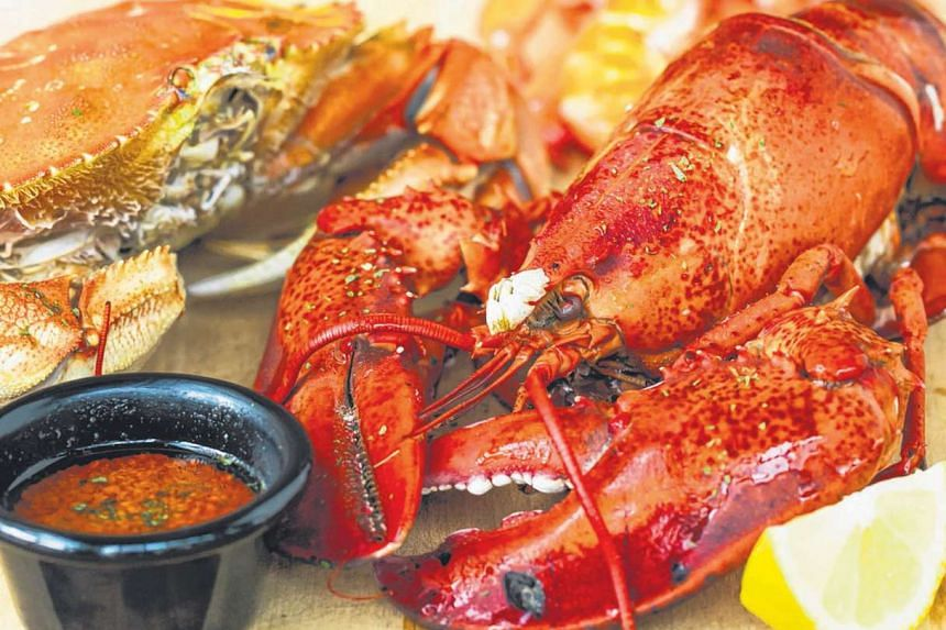 Enjoy Boston Lobsters (above) cooked in bags and then set on paper-lined tables at The Boiler Louisiana.