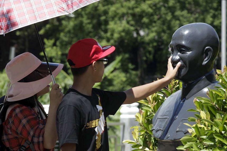 A person touching a bust of Taiwan's former ruler Chiang Kai-shek i Taoyuan on July 5.
