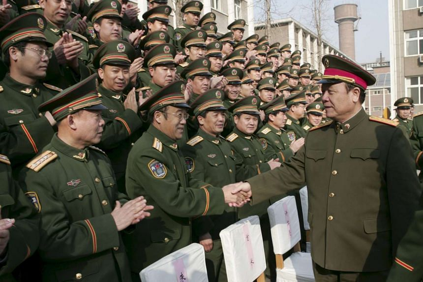 Former Chinese Central Military Commission vice-chairman Guo Boxiong (right) shaking hands with military officers in Shijiazhuang, Hebei province, China, on Feb 1, 2007.