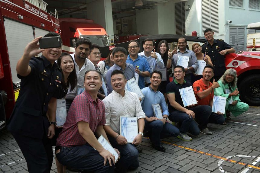 Lieutenant-Colonel Eric Chua (left), head of operations at the 1st SCDF Division with the award recipients who were among a group of about 30 good Samaritans who rushed to the aid of a pedestrian pinned under a truck on July 22, 2015.