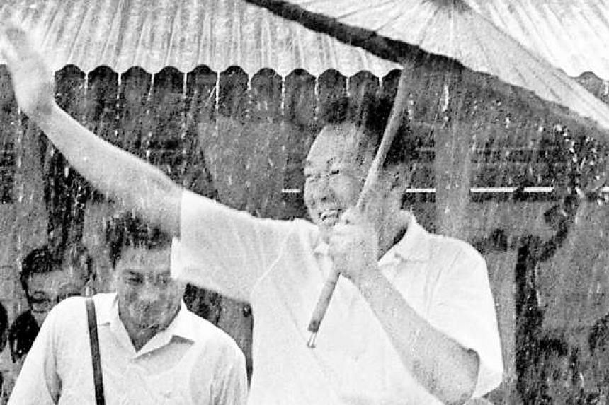 Mr Lee Kuan Yew braving the rain at the opening of the new People's Action Party branch at Pulau Bukom Kechil in 1966.
